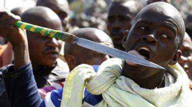 A protester licks his spear outside a South African mine in Rustenburg, northwest of Johannesburg. Striking miners armed with machetes and sticks at Lonmin's Marikana platinum mine.